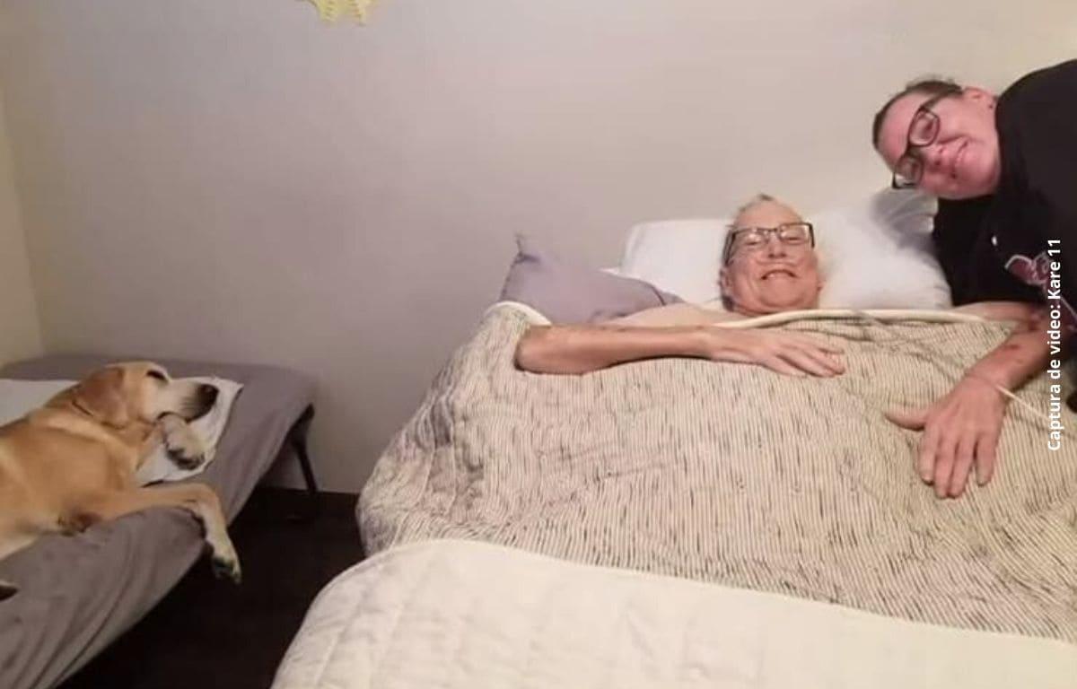 un hombre acostado en una cama, una mujer sonrie a su lado, un perro duerme en una cama