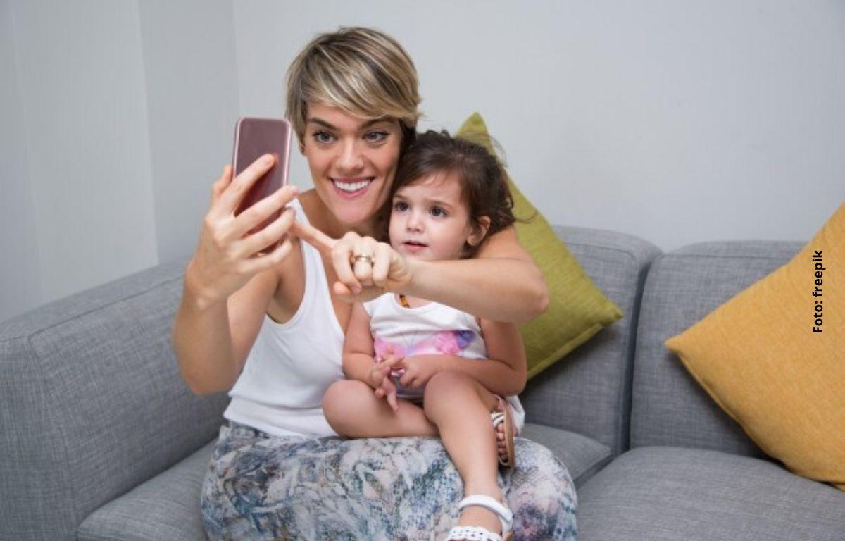 una mujer tomándose una fotografía con una niña