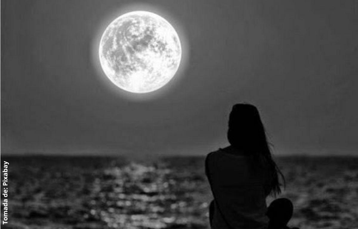 mujer viendo la luna llena frente al mar