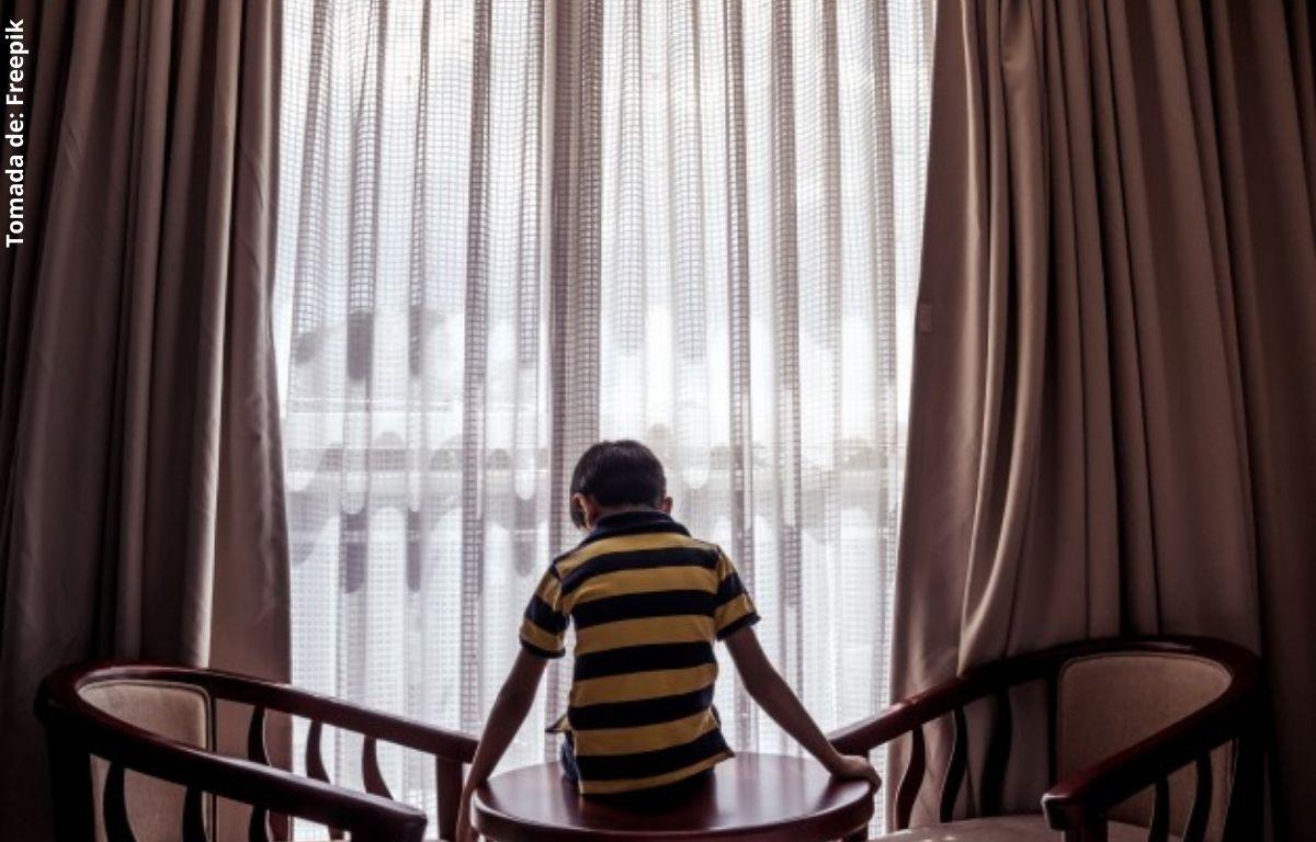 niño sentado en una mesa frente a una ventana
