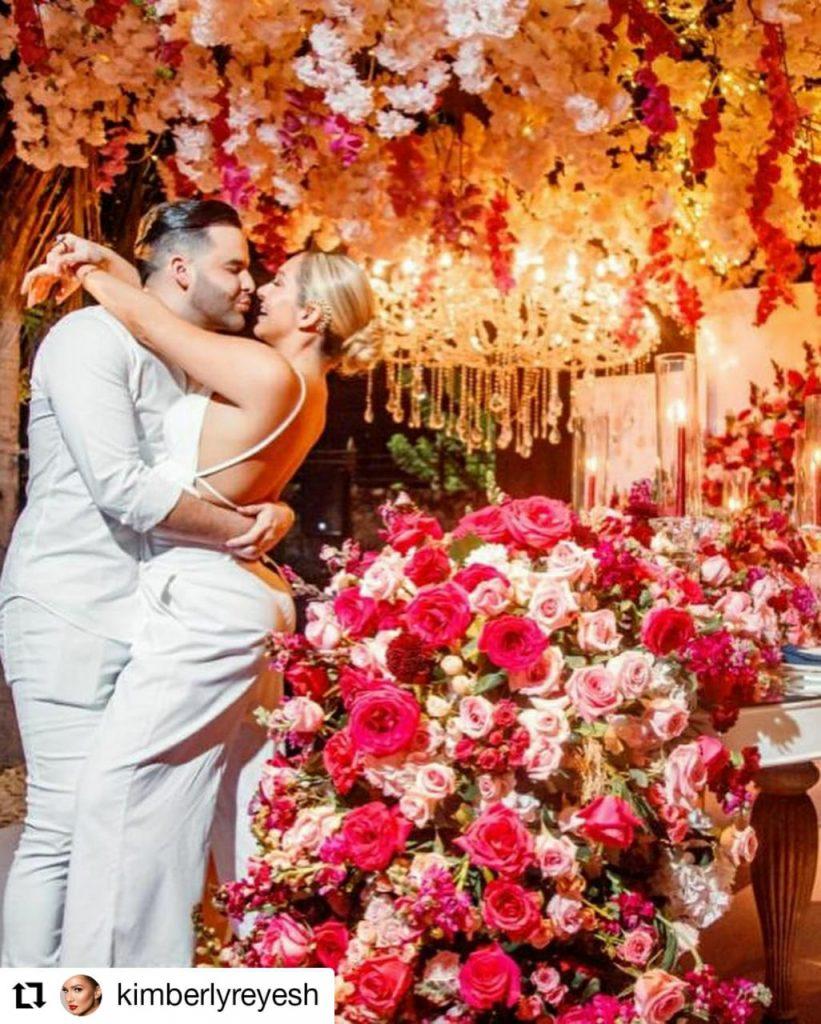 dos personas abrazadas con arreglos florales a su alrededor