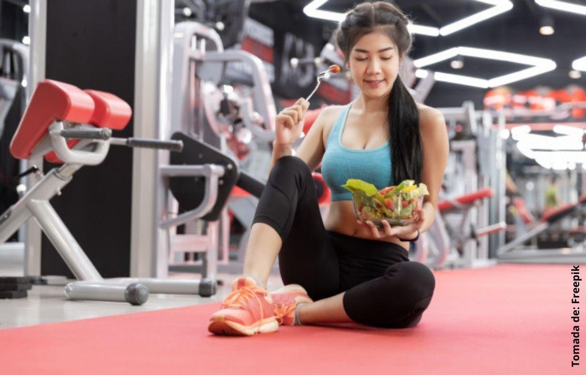 mujer en un gimnasio comiendo