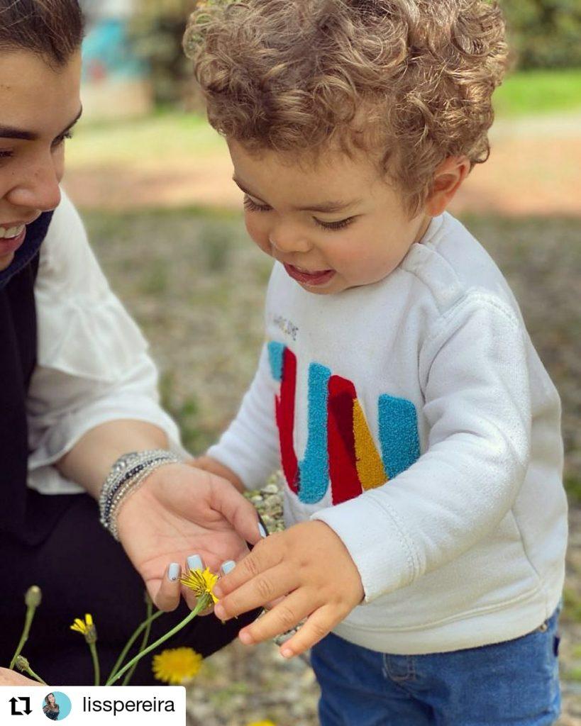 foto de una mujer con un niño viendo una flor