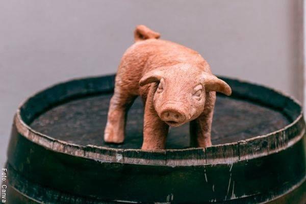 Foto de una figura de un marrano en arcilla sobre un barril