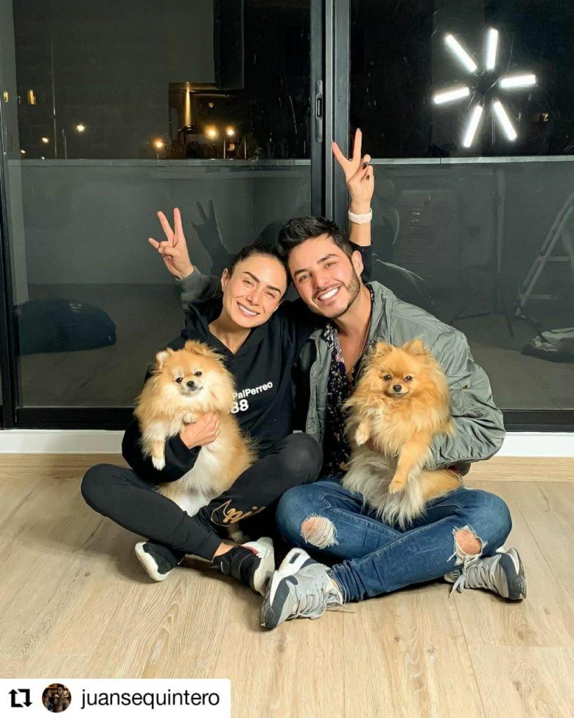 foto de un hombre, una mujer sonriendo mientras tienen dos perros