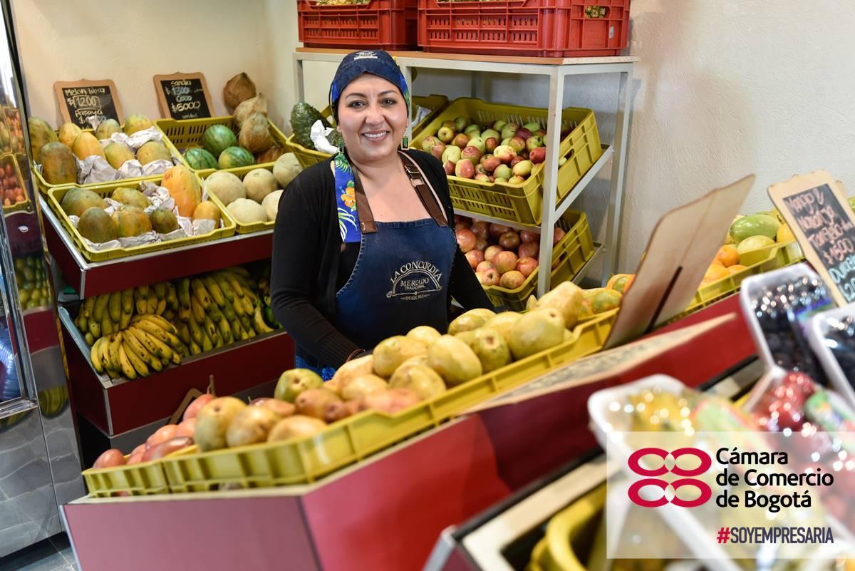 Mujer en su puesto de verduras y frutas