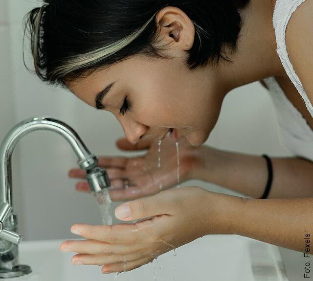 foto de mujer lavándose la cara después de hacerse mascarilla de café