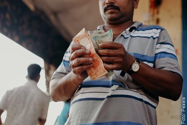 foto de un hombre contando dinero por soñar con peces