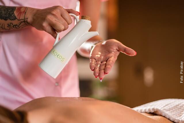 foto de masajista con aceite de coco