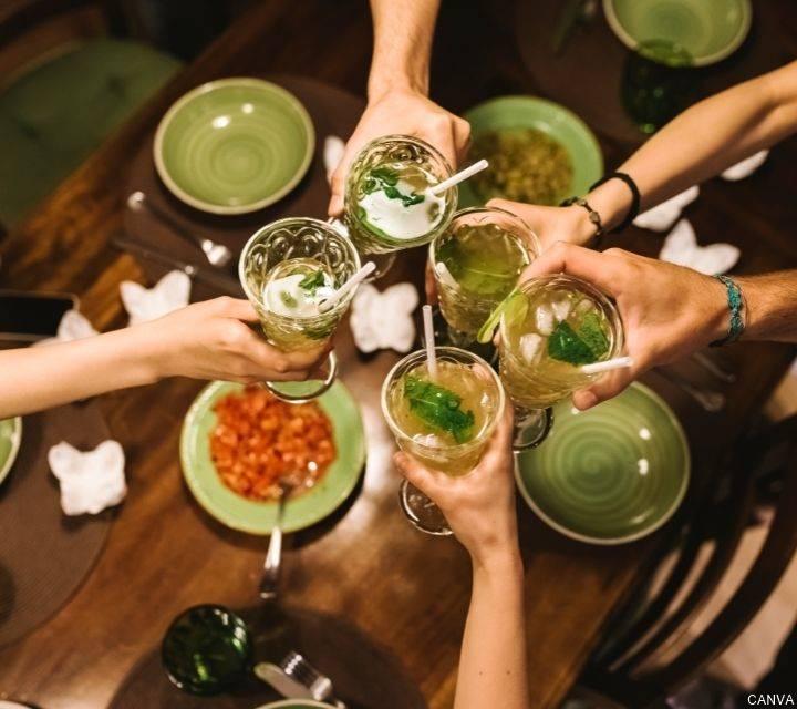 Foto cenital de manos con copas de licor y brindando